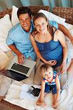 Family using laptop and smiling
