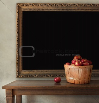 Fresh apples on wooden table with blackboard