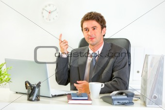 Sitting at office desk modern businessman got idea