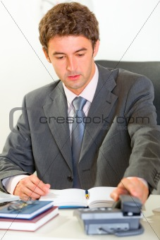 Sitting at office desk modern businessman pick up phone