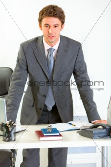 Portrait of confident modern businessman holding hands on office desk