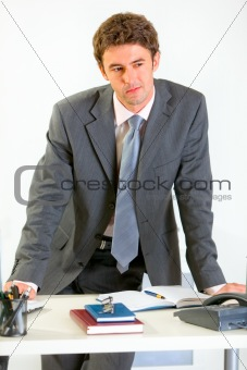 Portrait of thoughtful modern businessman holding hands on office desk
