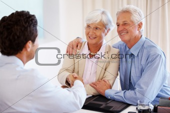 Senior couple shakes hands with their financial advisor