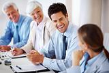 Smiling businessman sitting in meeting with colleagues