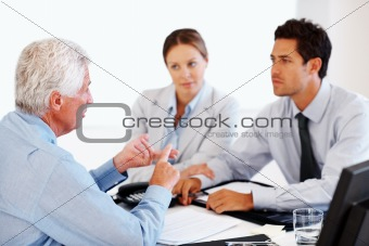 Agent advising to a young couple at office 