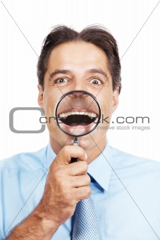 Mature business man with magnifier glass in front of his mouth