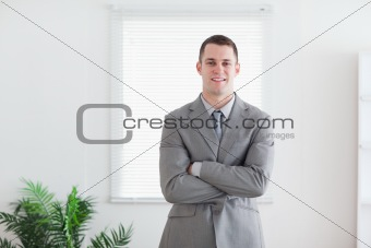 Smiling business man with his arms folded