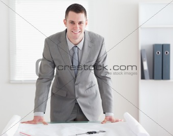 Smiling architect standing behind a table