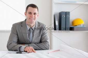 Smiling architect sitting behind a table