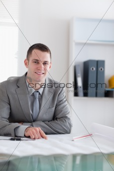 Close up of smiling architect sitting behind a table