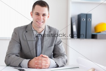 Smiling architect with folded hands