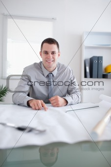 Close up of smiling architect working on a construction plan