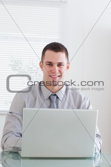 Close up of smiling businessman working on his laptop