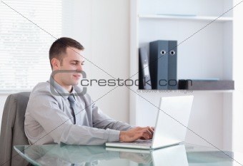 Satisfied businessman working on his notebook