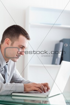 Smiling businessman typing on his notebook