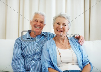 Happy old couple sitting together on sofa