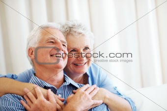 Smiling old couple looking away at copyspace
