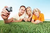 Happy family lying on grass taking snap on cellphone