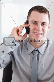 Close up of smiling businessman getting good news on the phone