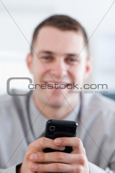 Close up of cellphone being held by smiling businessman