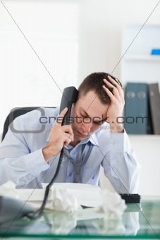 Close up of businessman looking at an invoice while on the phone