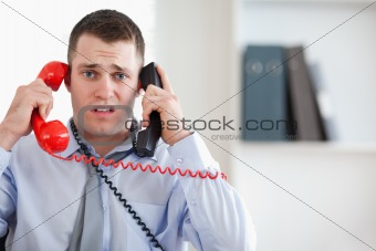 Close up of businessman unable to cope with the telephone