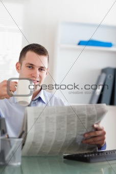 Smiling businessman reading the newspaper and having a coffee