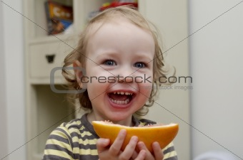 little girl laughing and eating grapefruit