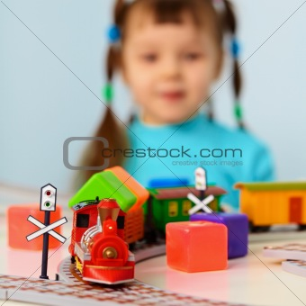 Little girl with toy railroad