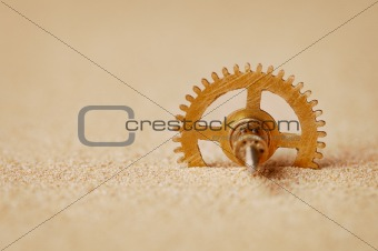 Clock detail - a gear in the sand
