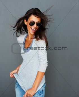 Windswept woman tugging at shirt