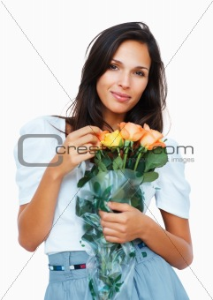 Sensual woman touching petal on bouquet of roses