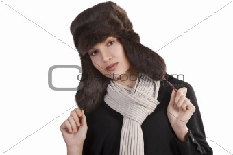 girl with fur hat and with scarf posing towards the camera