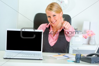 Smiling business woman showing laptops blank screen and thumbs up