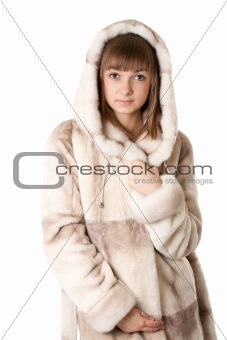 A beautiful young girl in a fur coat