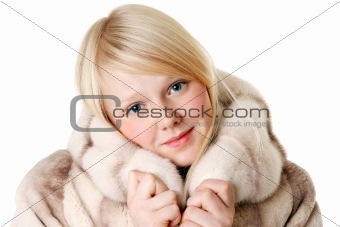 Blonde girl with blue eyes wearing a fur coat