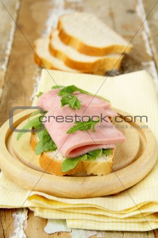 Delicious sandwich with ham on wooden table