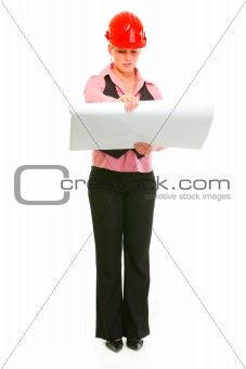 Full length portrait of modern architect woman checking plans