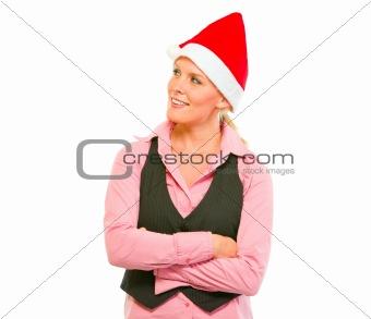 Portrait of smiling modern business woman in Santa Hat looking in corner