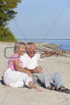 Happy Senior Couple Sitting Pointing on Beach