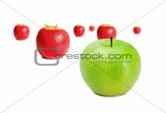 Green apple in front of red apples