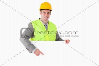 Smiling builder pointing at something