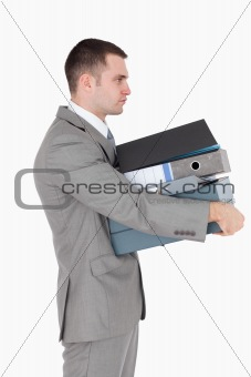 Portrait of a businessman holding a stack of binders