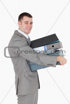 Portrait of a young businessman holding a stack of binders