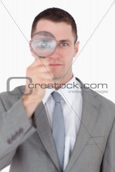 Portrait of a businessman looking through a magnifying glass