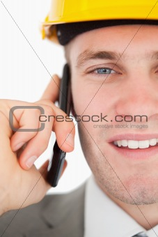 Close up of a smiling architect making a phone call