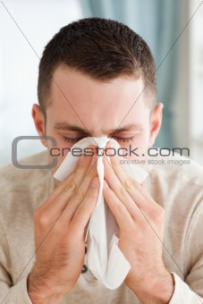 Portrait of a young man blowing his nose