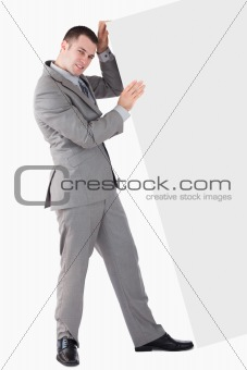 Portrait of young businessman pushing a blank panel