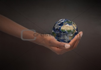 Feminine hand holding the Earth
