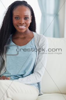 Close up of smiling woman sitting on sofa